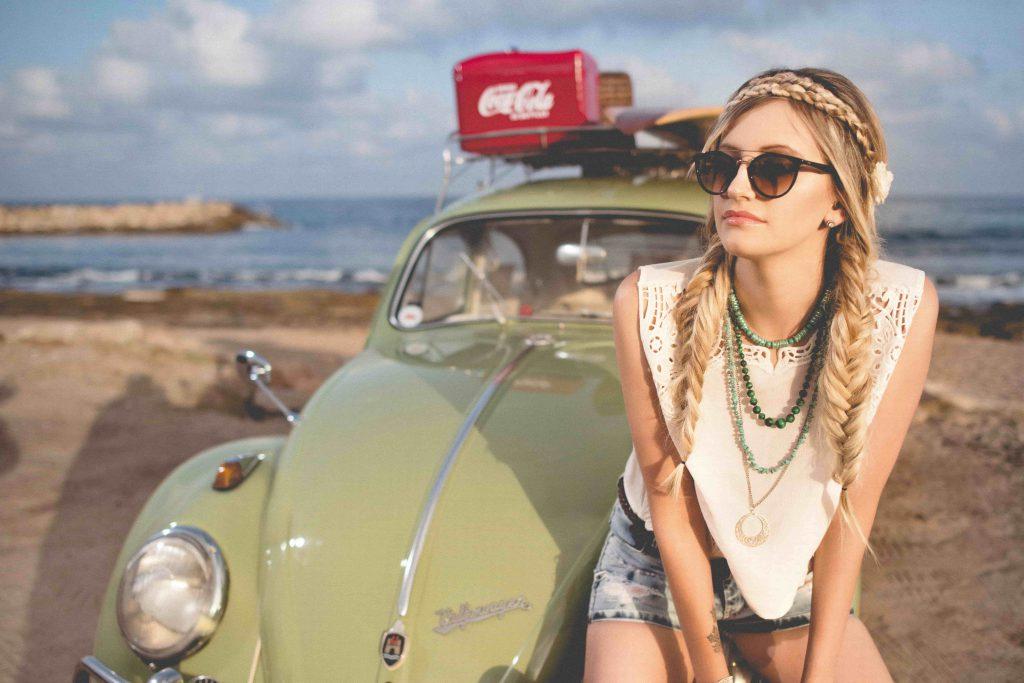 Jeune femme avec des tresses assise sur une voiture